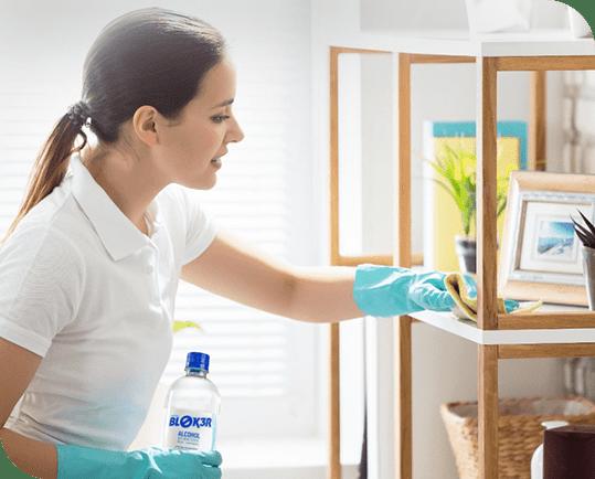 Mulher limpando estante com produtos da total bloker