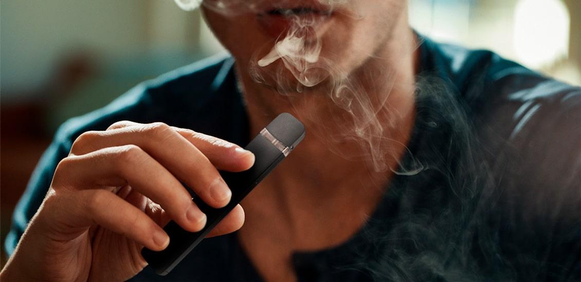 Device usb nas maos de um homem vaporando fumaça pela boca