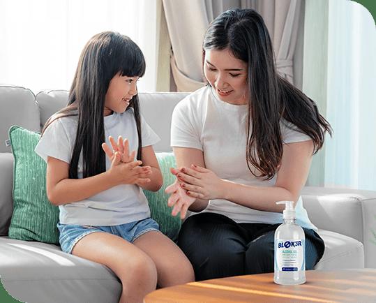 Foto de mãe e filha sentadas no sofá com alcool em gel na mesa